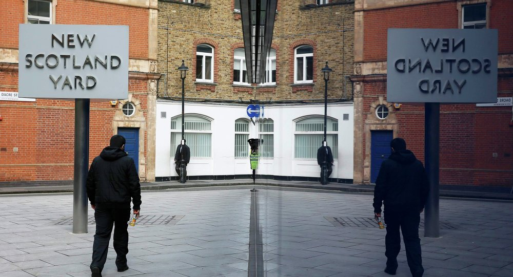 A man walks past the rotating triangular sign outside New Scotland Yard in central London March 17, 2015