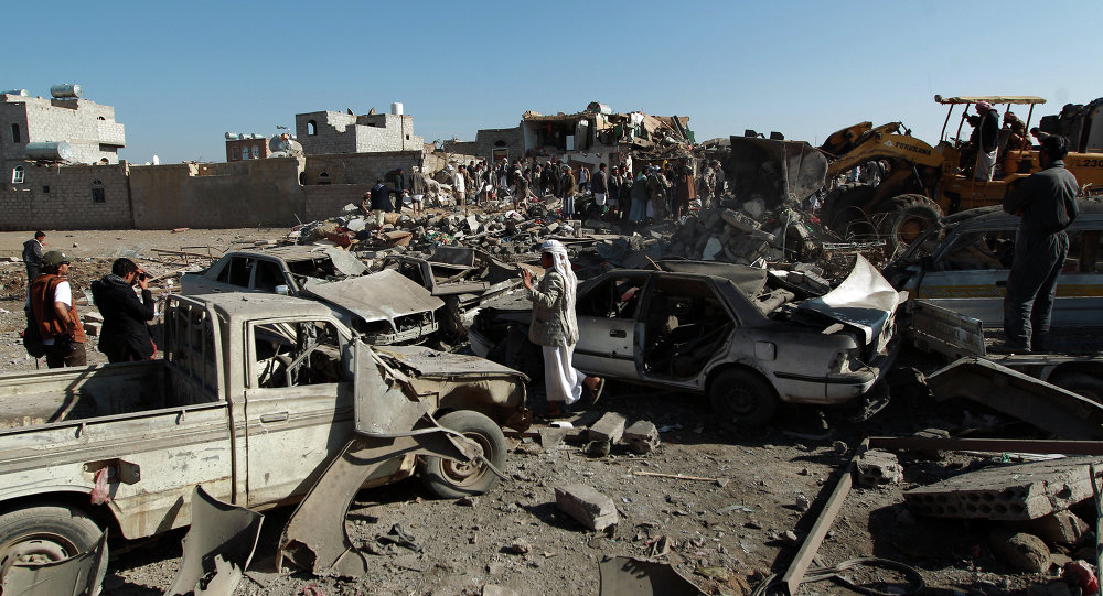 Yemenis stand at the site of a Saudi air strike against Huthi rebels near Sanaa Airport on March 26, 2015, which killed at least 13 people