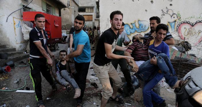 Palestinians help carry injured men following an Israeli Strike in Shijaiyah neighborhood, eastern Gaza City, last July.