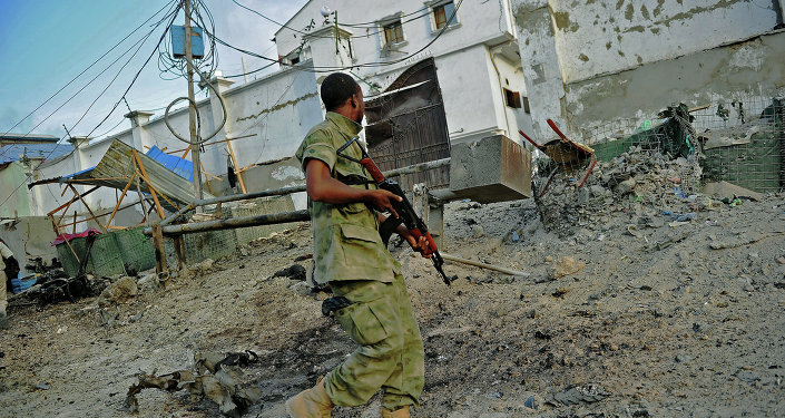 A solder walks past at the scene of a car bomb attack and armed raid by Al Shebab militants on the Maka al Mukarama hotel in Mogadishu