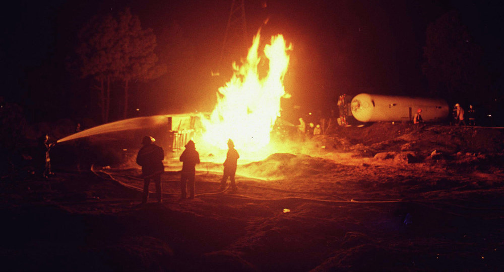 Firefighters try to extinguish a fire in a gas tanker truck