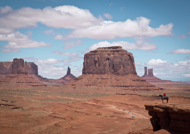 A Navajo man on a horse poses for tourists in front of the Merrick Butte in Monument Valley Navajo Tribal park, Utah, on May 12, 2014
