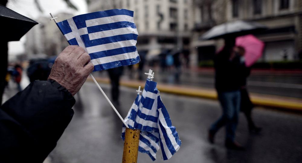 A man picks up a Greek flag placed on a street pole after a military parade in central Athens marking the Greek Independence Day on March 25, 2015