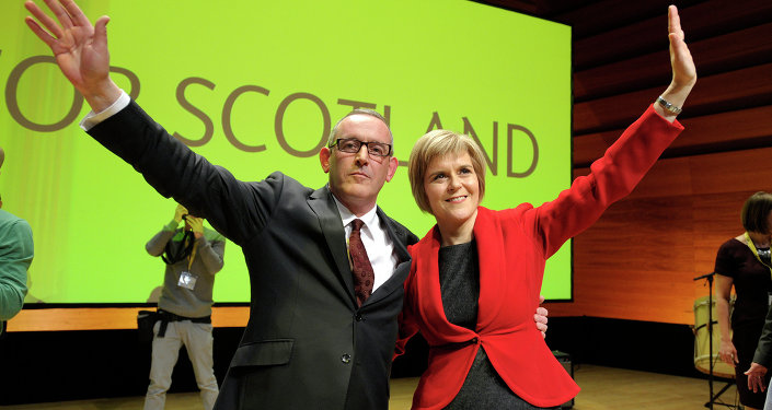 New leader of the Scottish National Party (SNP) Nicola Sturgeon (R) and new deputy SNP leader Stewart Hosie (L) wave to the audience after she delivers her first keynote speech at the SNP Conference in Perth, Scotland