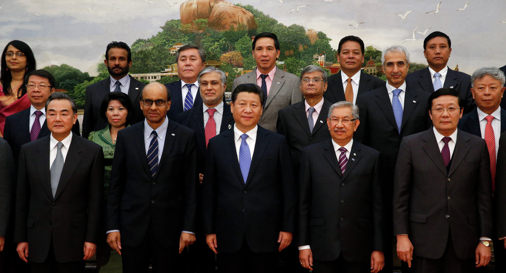 Chinese President Xi Jinping (C) takes photos with guests of the Asian Infrastructure Investment Bank at the Great Hall of the People in Beijing on October 24, 2014.
