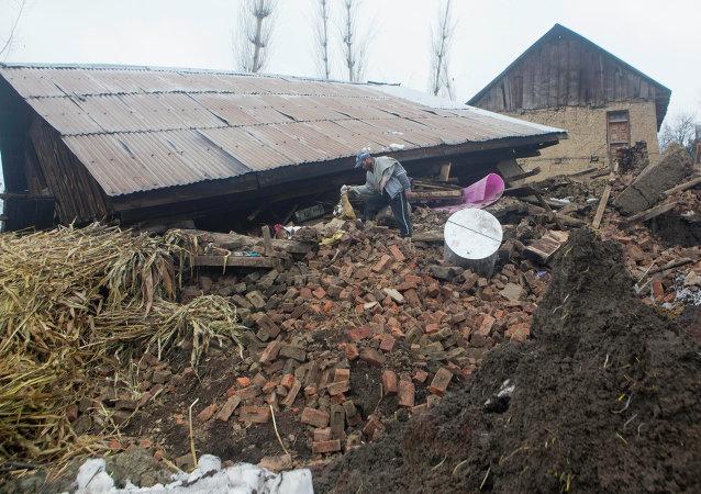 A Kashmiri villager inspects a damaged house following landslides