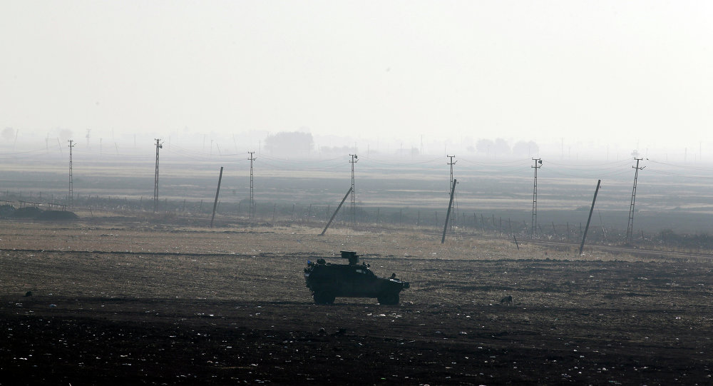 A Turkish forces armoured vehicle is stationed along the border road in Mursitpinar, nn the outskirts of Suruc, on the Turkey-Syria border