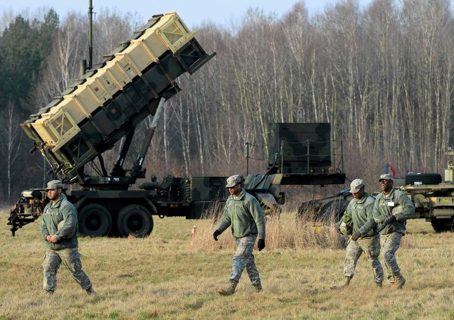 US soldiers walk next to a Patriot missile defence battery during join exercises at the military grouds in Sochaczew, near Warsaw