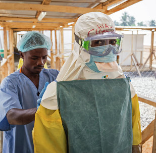 In this photo taken on Monday, March 2, 2015, a health care worker prepares a colleague's virus protective gear before entering a high risk zone at an Ebola virus clinic operated by the International Medical Corps in Makeni, Sierra Leone