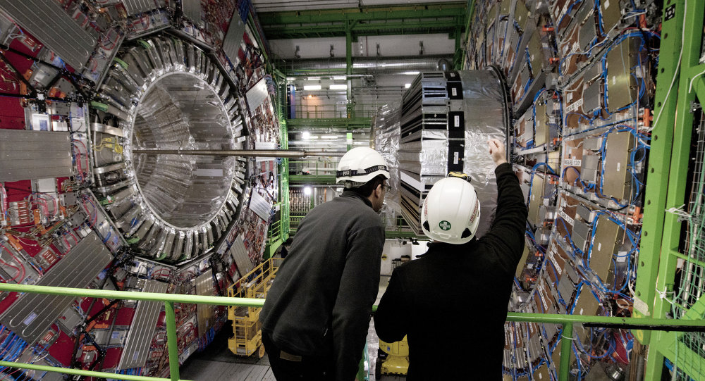 Workers gesture on February 10, 2015 in front of the CMS (Compact Muon Solenoid) Cavern at the European Organisation for Nuclear Research (CERN) in Meyrin, near Geneva