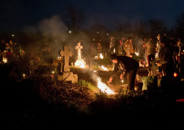 People stand by fires they lit by a relative's grave in a cemetery during an Orthodox Palm Sunday memorial for the departed in Herasti, southern Romania, early Sunday, April 5, 2015