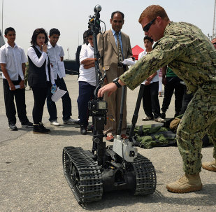 Explosive Ordnance Disposal Technician 2nd Class Blake Fletcher assigned to Commander, Task Group (CTG) 56.1, explains the capabilities of a bomb disposal robot.