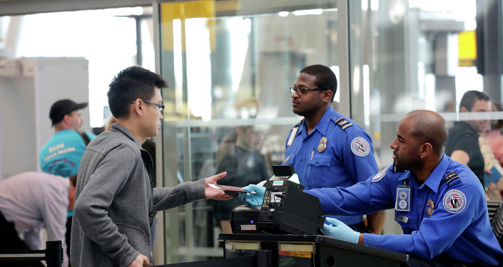A traveler, left, hands his documents to a Transportation Security Administration officer as part of security screening at John F. Kennedy International Airport.