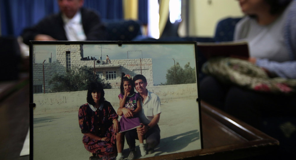 Ghassan Jarrar (background), the husband of Khalida Jarrar (portrait-L), a member of the Popular Front for the Liberation of Palestine (PFLP), sits behind a family picture on April 2, 2015 at their home in the West Bank city of Ramallah, where she was arrested the day before