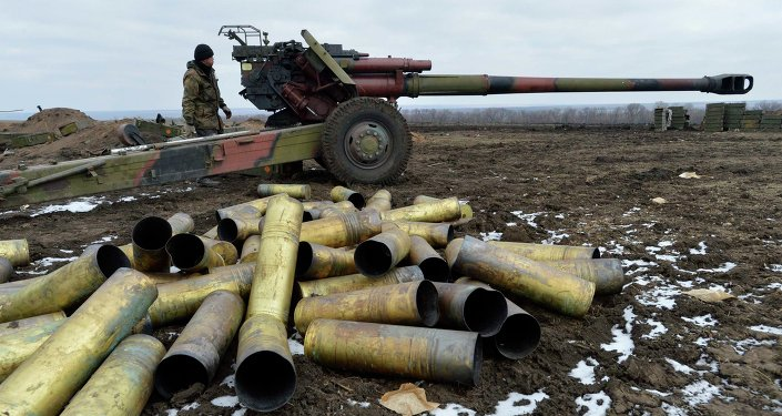 A member of the Ukrainian armed forces stands near a cannon, with shell cases seen in the foreground, at positions in Donetsk region, eastern Ukraine