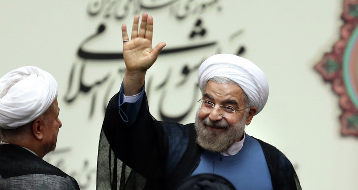 Iran's new President Hasan Rouhani, waves after swearing in at the parliament, in Tehran, Iran