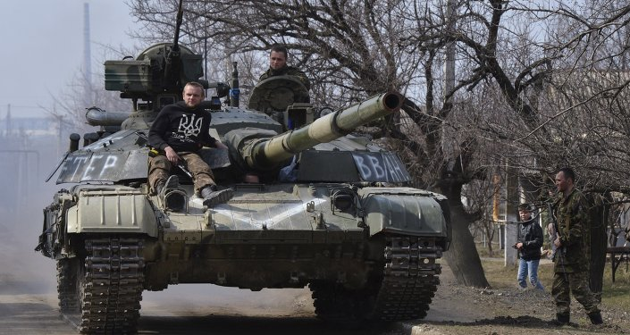 Members of the Ukrainian armed forces drive a tank in the settlement of Luhanske, Donetsk region, March 27, 2015.