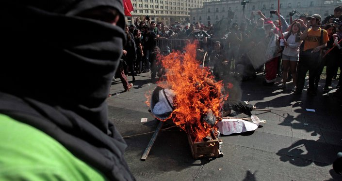 A masked demonstrator stands next to a pile of debris set on fire during a protest near La Moneda Palace in Santiago, Chile, Thursday, April 16, 2015. Thousands of students marched through the streets of Chile's capital to protest recent corruption scandals and to complain about delays in a promised education overhaul. While it was largely peaceful, violence broke out at the end when hooded protesters threw rocks and gasoline bombs at police. At least one officer was injured.