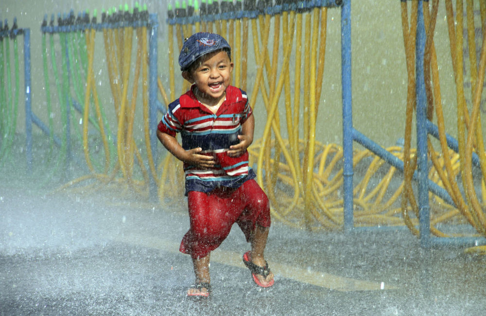 A boy runs as he is sprayed with water during the opening ceremony of the annual Thingyan water festival celebrations outside Yangon City Hall in Yangon, Myanmar Monday, April 13, 2015. Myanmar began celebrating its annual days-long water festival, known as Thingyan, on Monday, marking the new year according to the traditional Burmese lunisolar calendar.
