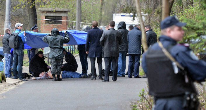 Crime experts and police officers work on the site of the opposition journalist Oles Buzina murder in Kiev