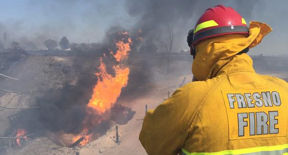 A firefighter watches a blaze which broke out when a gas line exploded near Fresno, California