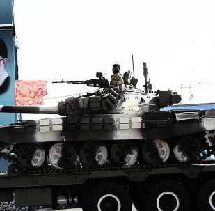 An Iranian soldier sitting atop a T-72 tank as it rolls past a portrait of Iran's supreme leader, Ali Khamenei during the Army Day parade in Tehran on April 18, 2015.