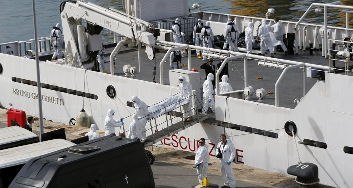 Italian coastguard and Armed Forces of Malta personnel in protective clothing carry the body of a dead immigrant off the ship Bruno Gregoretti in Senglea, in Valletta's Grand Harbour, April 20, 2015
