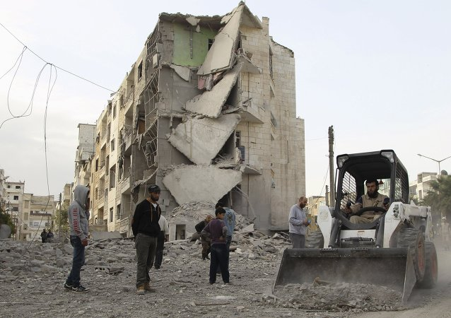 A man operates a front loader as he removes debris at a site hit by what activists said were barrel bombs dropped by forces of Syria's President Bashar al-Assad, at al-Thawra neighborhood in Idlib city April 20, 2015