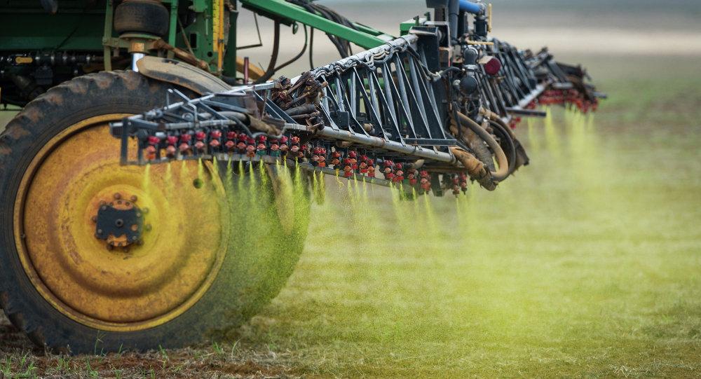 大豆畑に除草剤を散布する