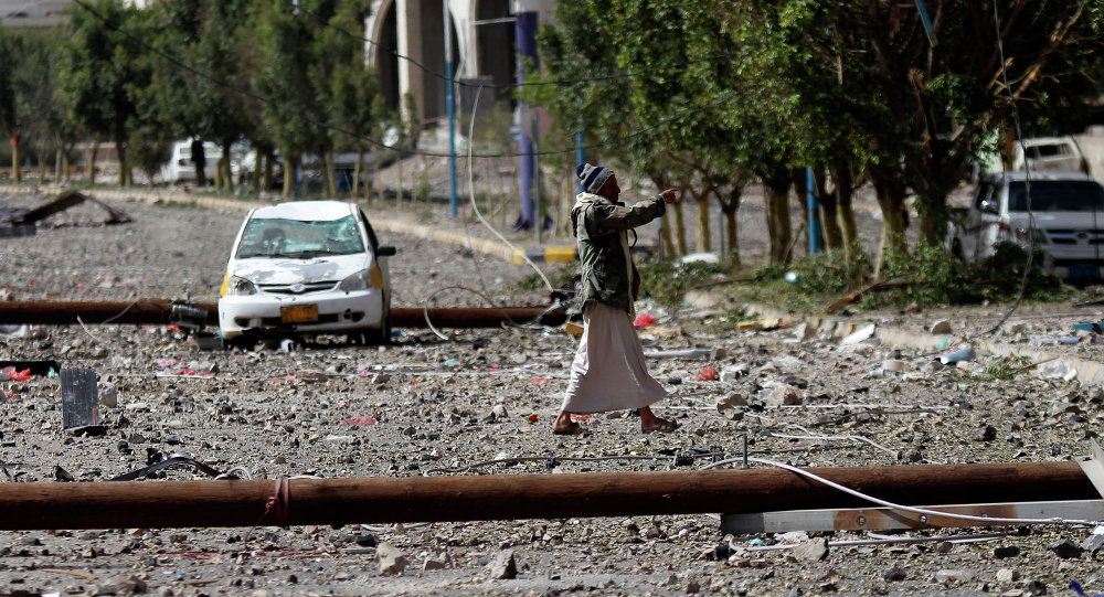 A Shiite fighter known as Houthi, walks on a street littered by debris after a Saudi-led airstrike hit a site where many believe the largest weapons cache in Yemen's capital, Sanaa, is located on Monday, April 20, 2015