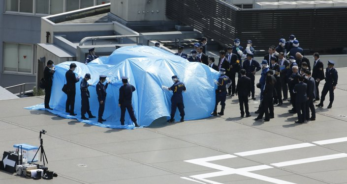 Police and security officials stand around a tarpaulin covering a drone on the roof of Prime Minister Shinzo Abe's official residence in Tokyo April 22, 2015