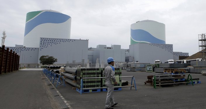 An employee of Kyushu Electric Power Co walks in front of reactor buildings at the company's Sendai nuclear power plant in Satsumasendai, Kagoshima prefecture