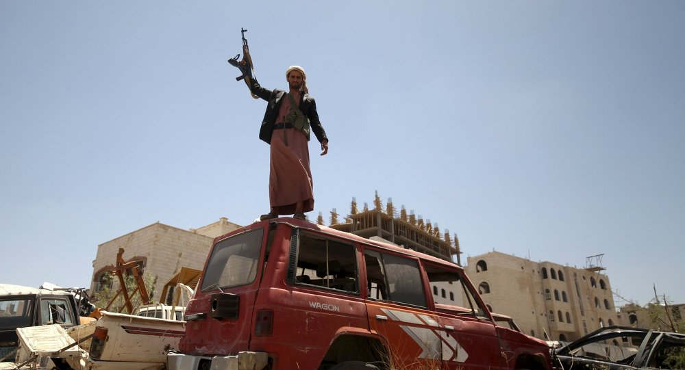 A follower of the Houthi group raises his weapon as he stands on a vehicle on a damaged street, caused by an April 20 air strike that hit a nearby army weapons depot, in Sanaa April 21, 2015