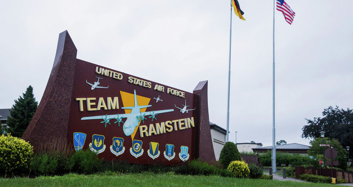 The US and German flags fly behind a sign at Ramstein Air Base, Germany.