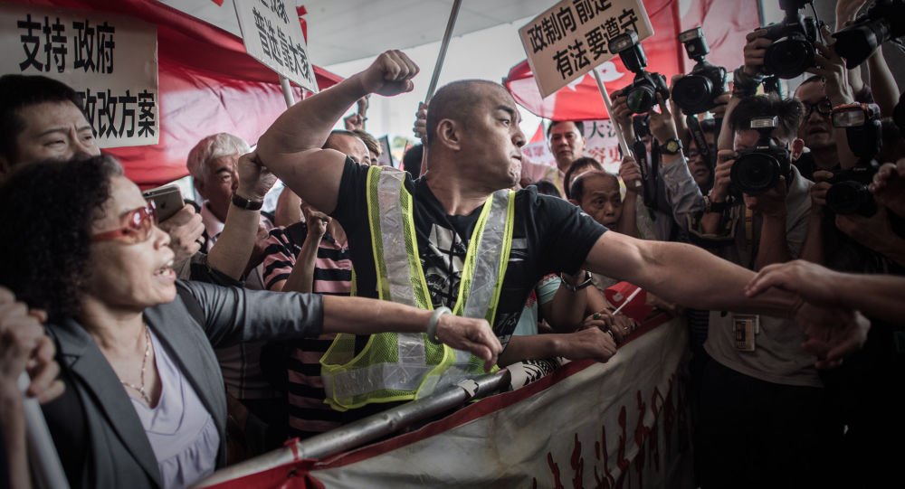 A pro-Beijing protester tries to punch a pro-democracy demonstrator after a heated argument outside the government building in Hong Kong on April 22, 2015.