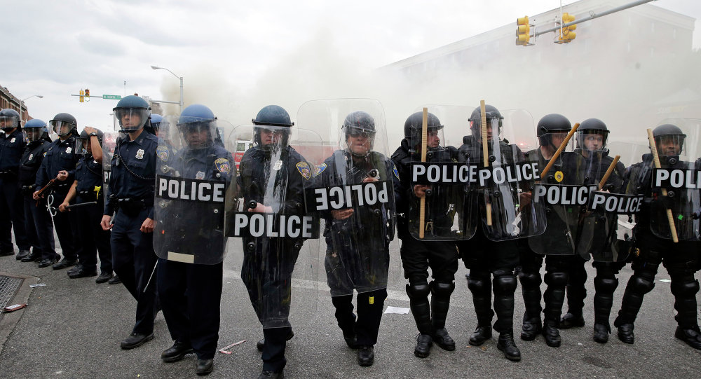 Police advance toward protestors as a store burns, Monday, April 27, 2015, during unrest following the funeral of Freddie Gray in Baltimore.