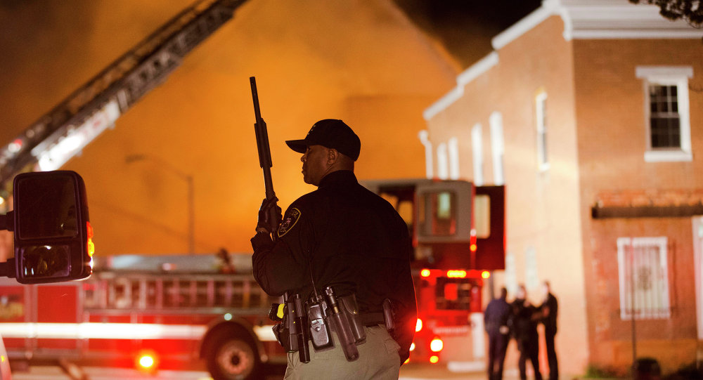 An officer stands near a blaze, Monday, April 27, 2015, after rioters plunged part of Baltimore into chaos, torching a pharmacy, setting police cars ablaze and throwing bricks at officers.