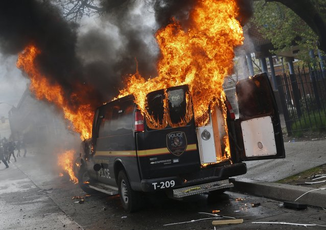 A Baltimore Metropolitan Police transport vehicle burns during clashes in Baltimore, Maryland April 27, 2015