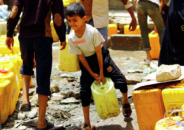 A Yemeni boy carries a jerrycans filled with water from a public tap amid an acute shortage of water supply to houses in the capital Sanaa.