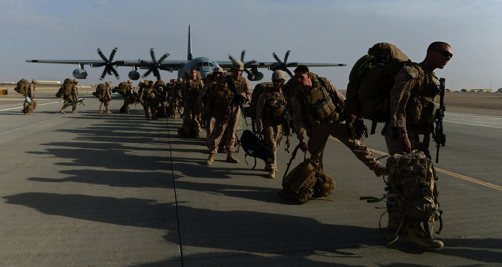 US Marines walk in line after arriving in Kandahar on October 27, 2014, as British and US forces withdraw from the Camp Bastion-Leatherneck complex in Helmand province
