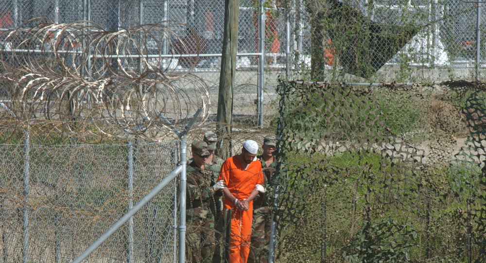 A detainee is escorted to interrogation by U.S. military guards at Camp X-Ray at Guantanamo Bay.