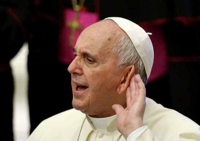 Pope Francis tries to hear during an audience with the members of Cursillos of Christianity movement in the Paul VI hall at the Vatican on April 30, 2015