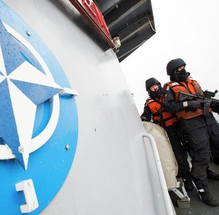 Two Norwegian sailors on board the Norwegian support vessel Valkyrien pose for photographers next to the NATO logo