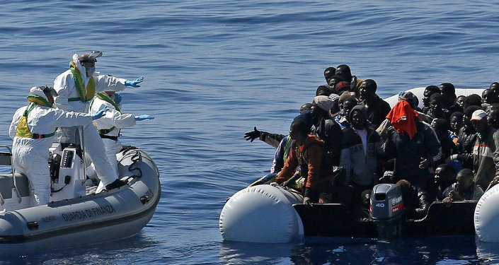 Italian Financial Police rescue unit approaches an inflatable dinghy crowded with migrants off the Libyan coast, in the Mediterranean Sea, Wednesday, April 22, 2015