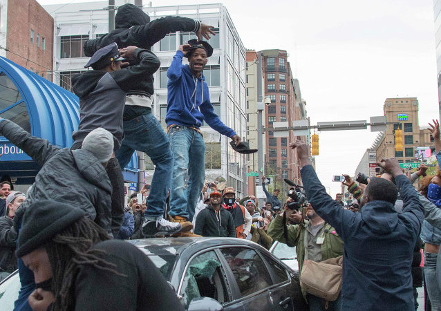 A demonstrator puts on a Baltimore City Police hat taken from a destroyed police car while protesting the death Freddie Gray, an African American man who died of spinal cord injuries in police custody, in Baltimore, Maryland, April 25, 2015