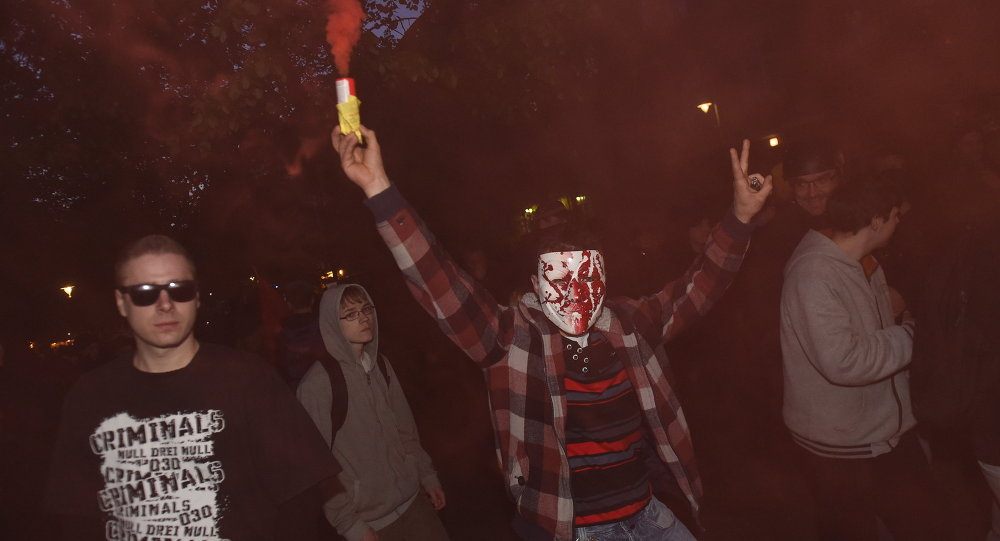 A masked protester lights a smoke-bomb during the 'Revolutionary' May Day demonstration in Berlin on May 1, 2015.