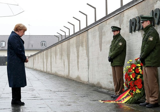 German Chancellor Angela Merkel observes a moment of silence as she lays a wreath during a ceremony at the memorial in the former German Nazi concentration camp in Dachau near Munich, Germany May 3, 2015