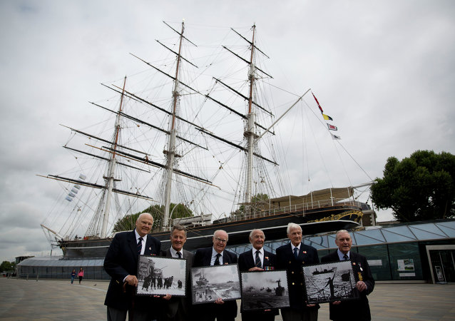 Veterans who served in Britain's Merchant Navy pose with a selection of Royal Mail Merchant Navy stamps during a launch at the Cutty Sark clipper vessel in London, Wednesday, Sept. 18, 2013