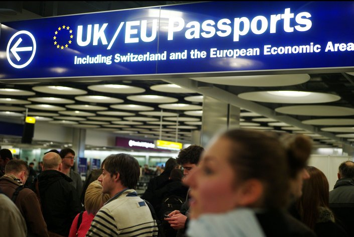Travellers at Heathrow queue to have their passports checked at the UK border