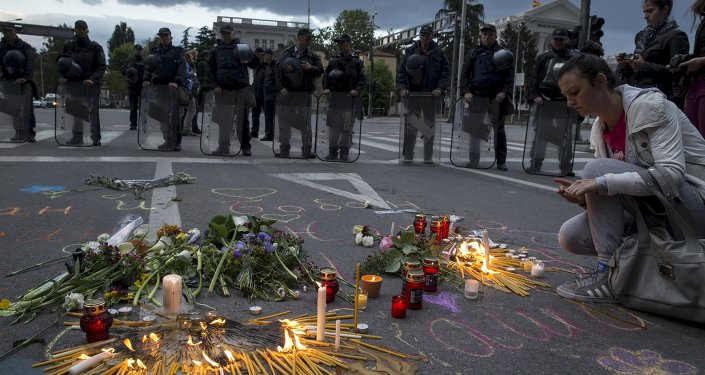 A woman lights a candle to commemorate policemen who were killed in a gun battle, during a memorial in Skopje, Macedonia, May 11, 2015.